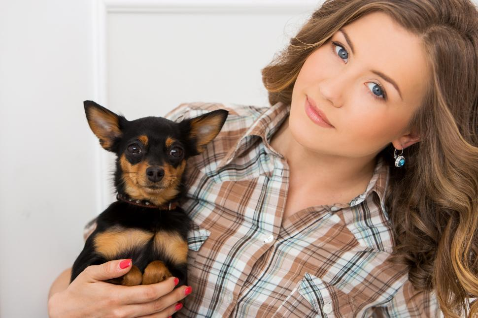 Download Free Stock Photo of Young woman holding a dog