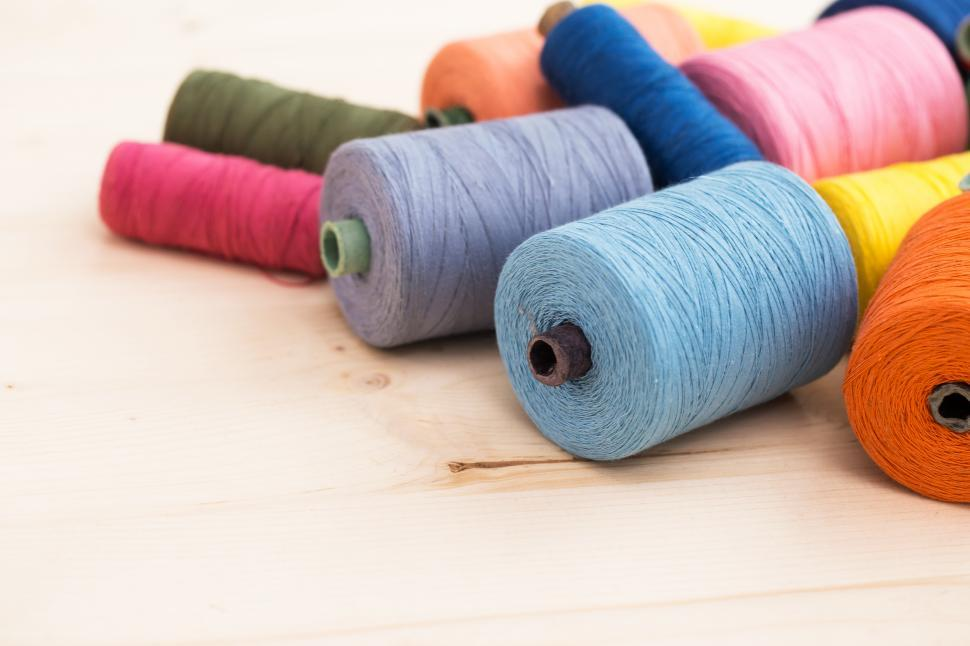 Download Free Stock Photo of Spools of colorful threads on the table