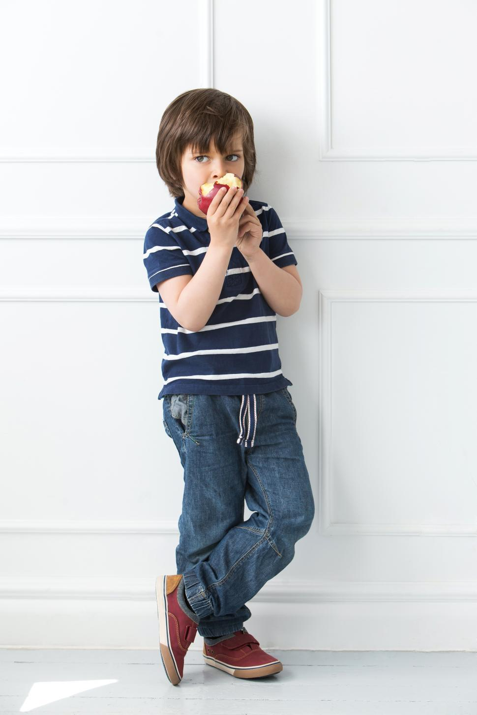 Download Free Stock Photo of Adorable kid standing and eating apple