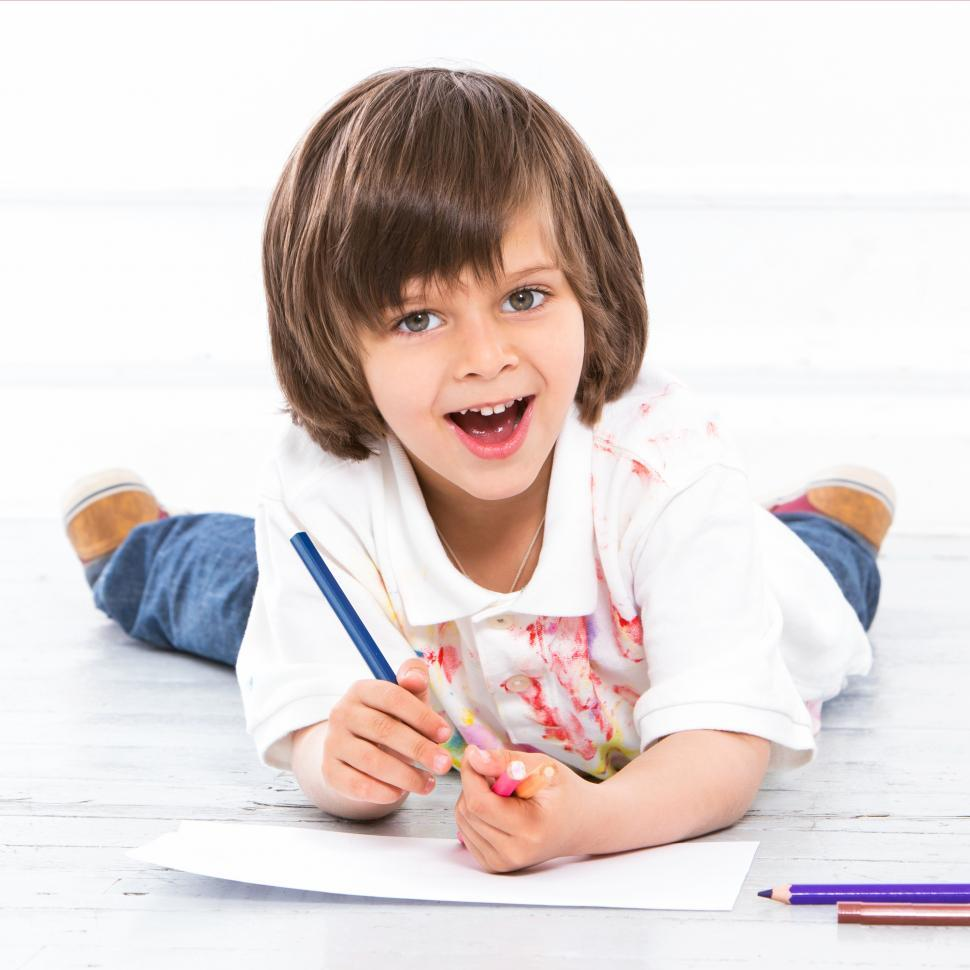Download Free Stock Photo of Adorable kid on the floor coloring