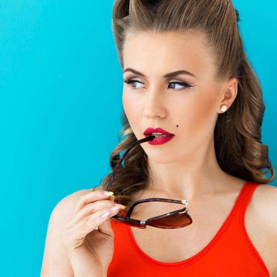 Download Free Stock Photo of Pinup. Girl in red swimsuit with glasses at lips