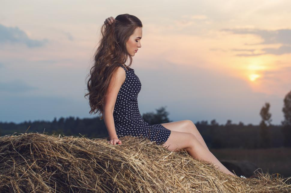 Download Free Stock Photo of Attractive young woman sitting on a rolled bale of hay