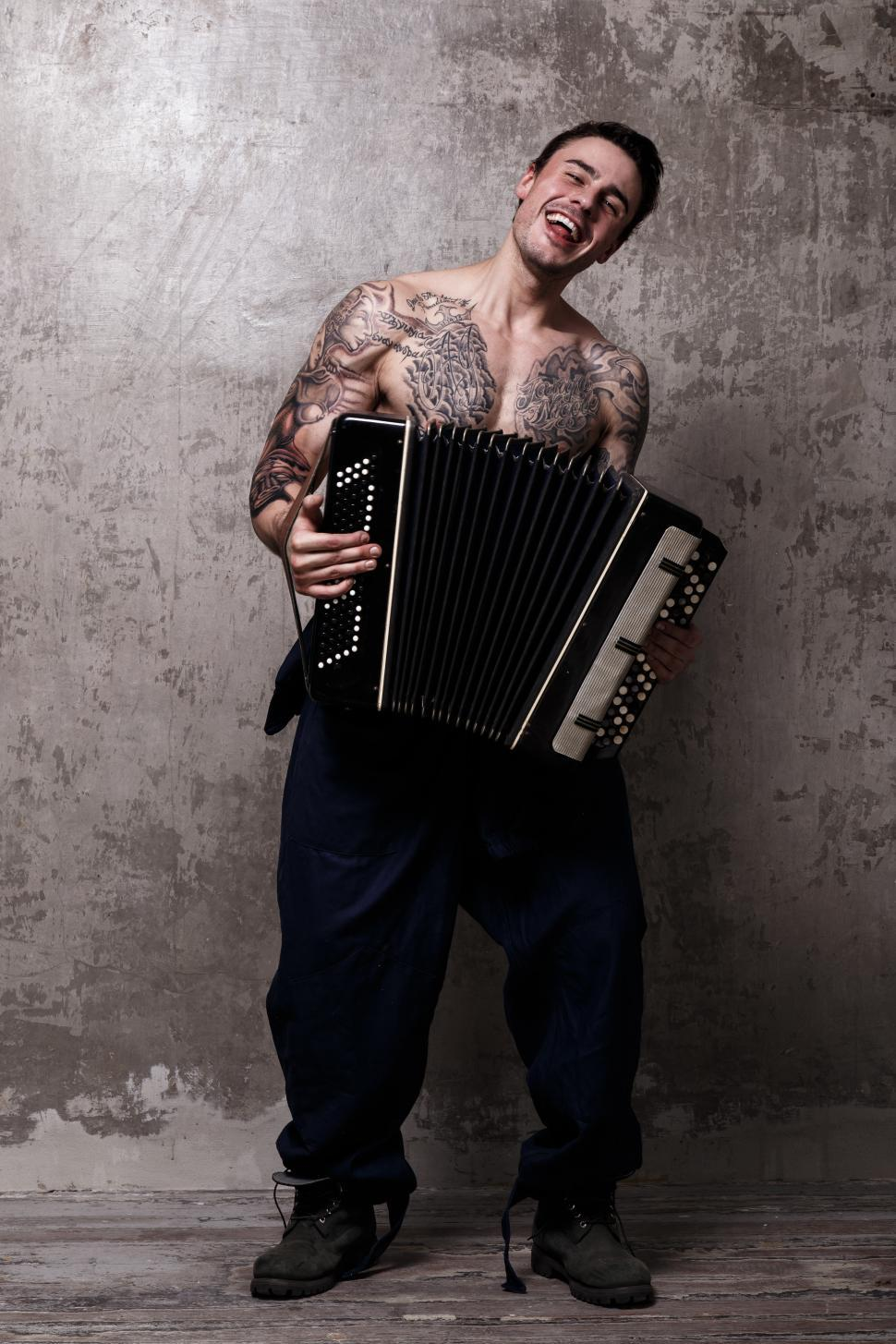 Download Free Stock Photo of Tattooed shirtless musician with accordion