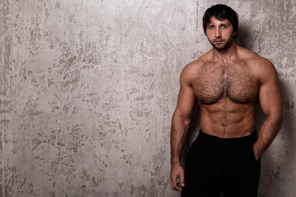 Download Free Stock Photo of Shirtless muscular guy against textured wall