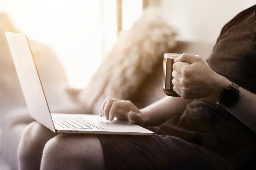 Download Free Stock Photo of Work From Home - Person with Coffee in Hand Working on Couch