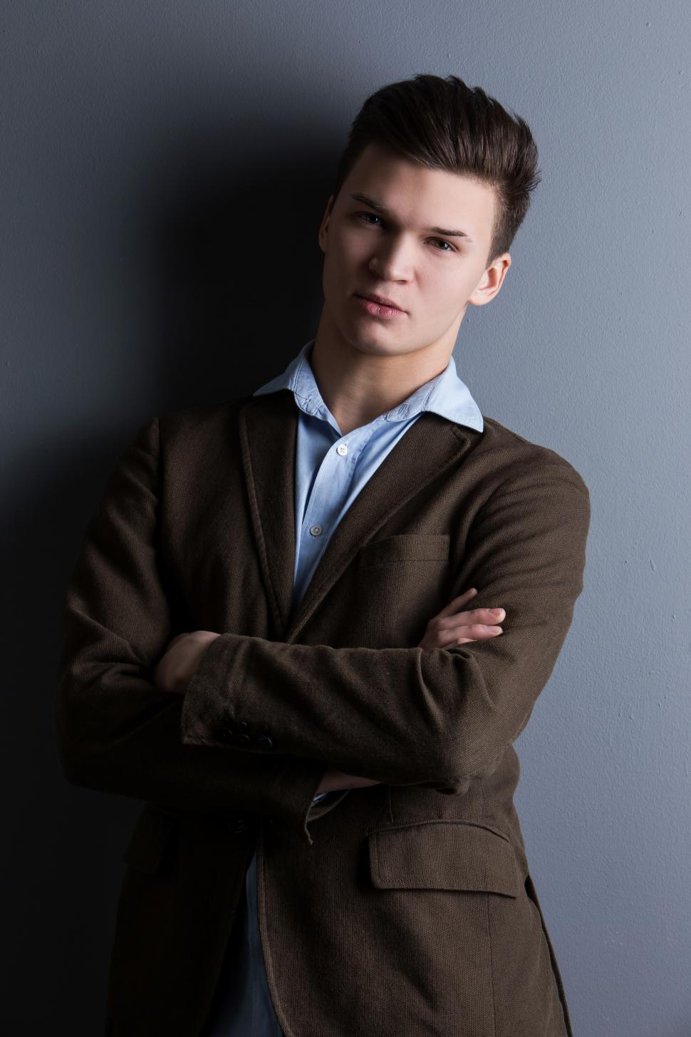 Download Free Stock Photo of Well-dressed man with arms crossed, leaning on wall