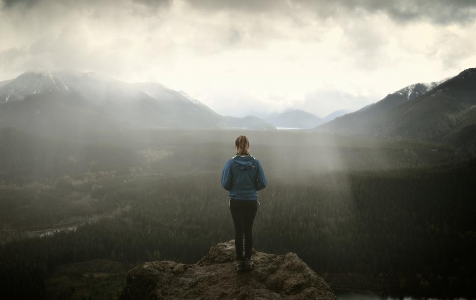 Download Free Stock Photo of Hiker on Rock Ledge over Foggy Dark Landscape
