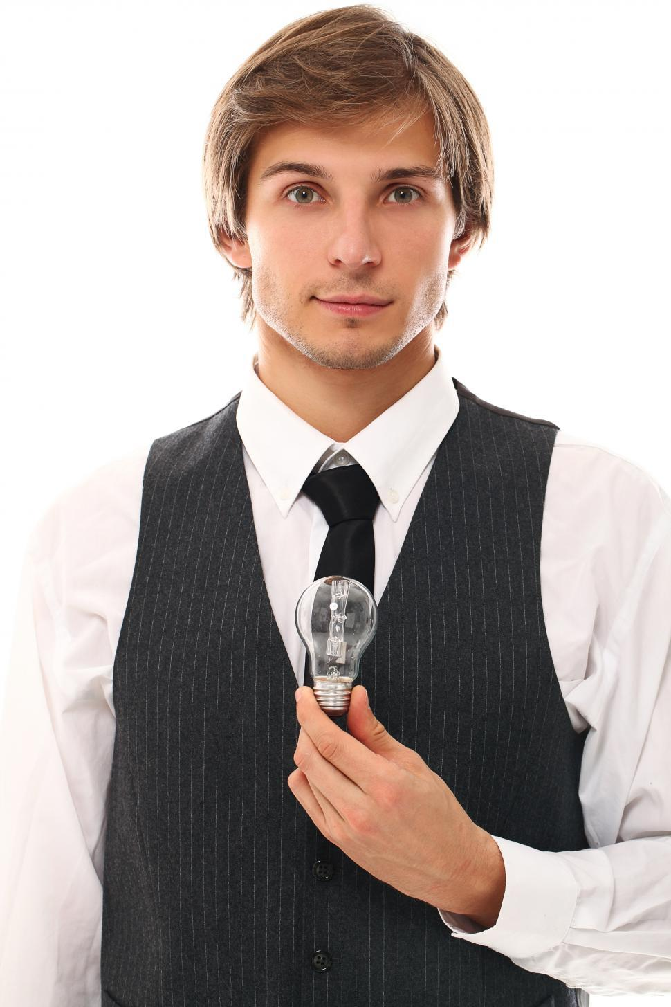 Download Free Stock Photo of Idea. Well dressed man holding a light bulb.