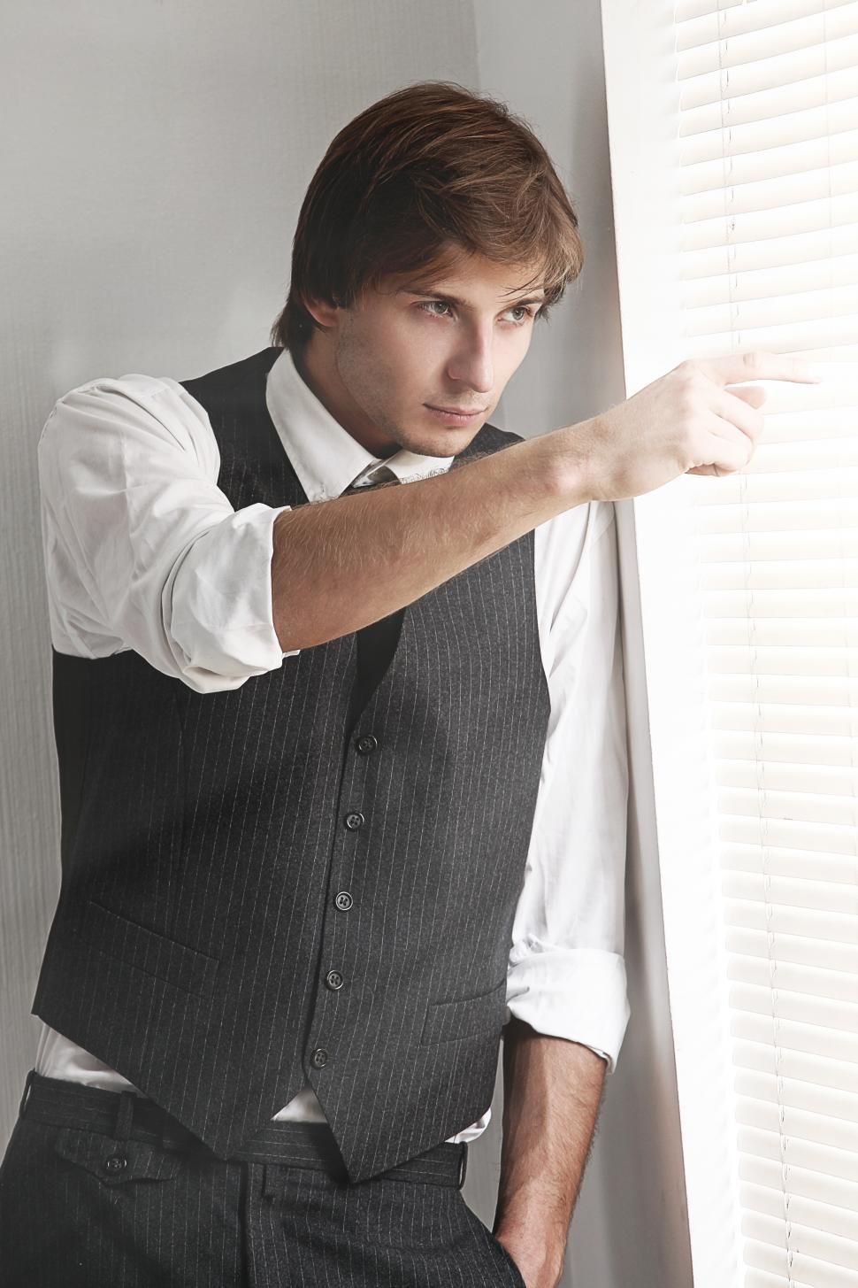 Download Free Stock Photo of Man in dark vest peering through the blinds