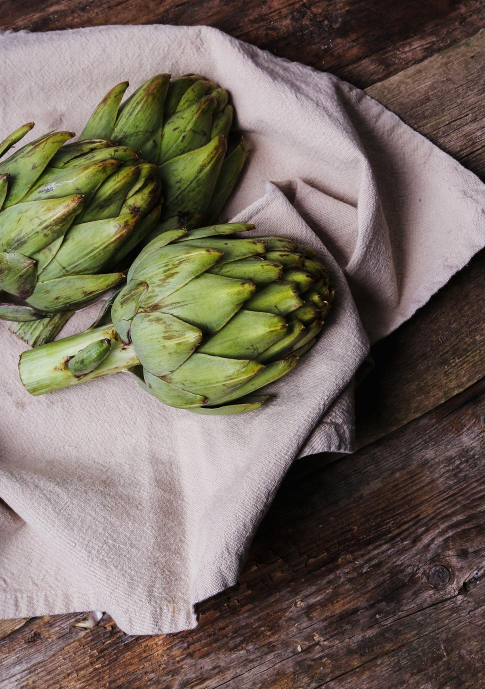 Download Free Stock Photo of Three Artichokes on natural fabric