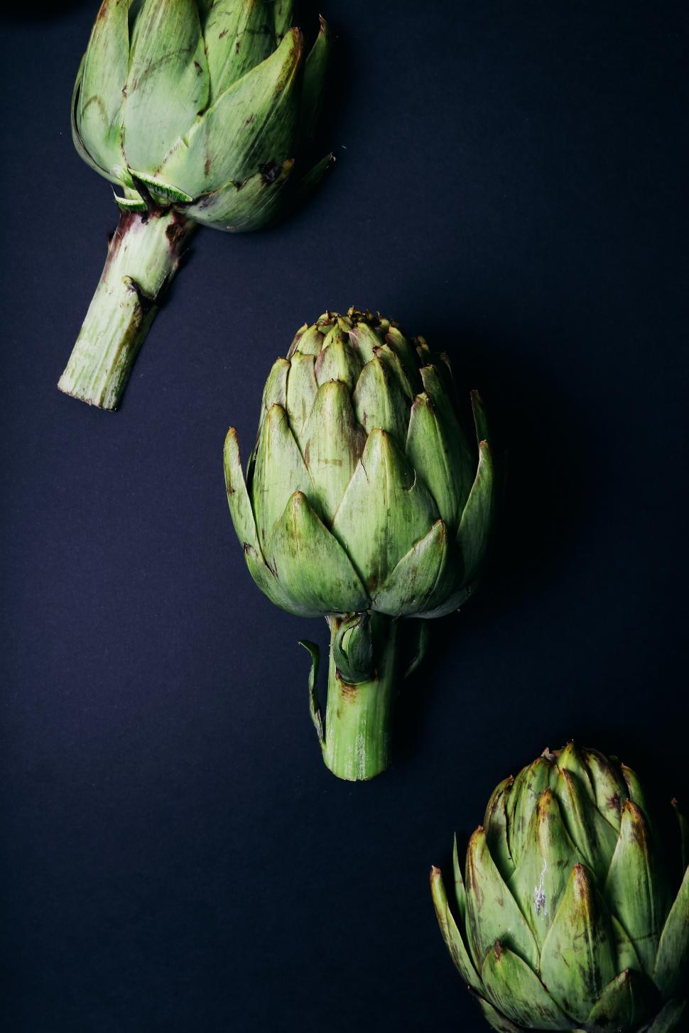 Download Free Stock Photo of Artichokes arranged on a dark background