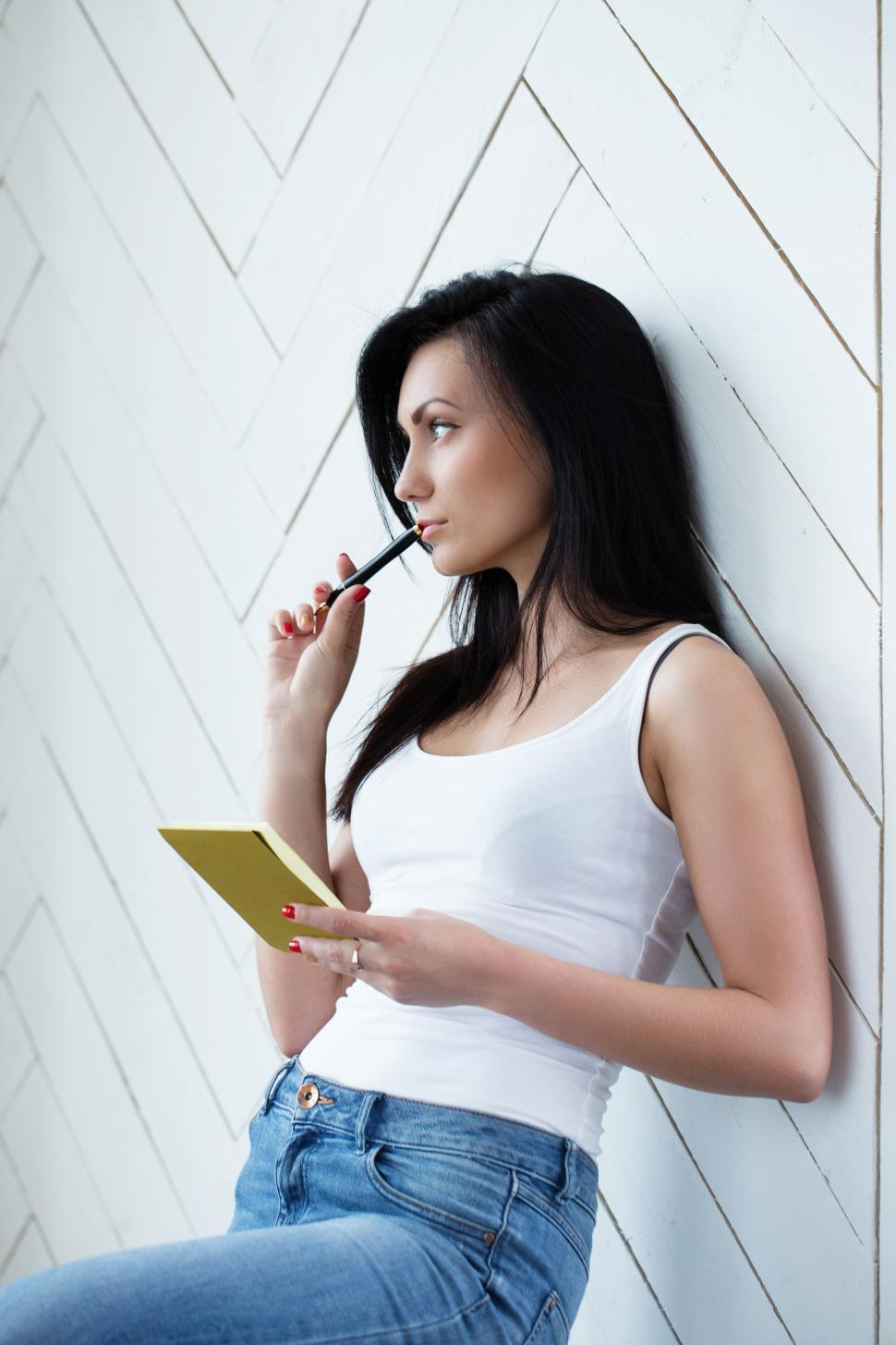 Download Free Stock Photo of Young woman thoughtfully chewing on her pen