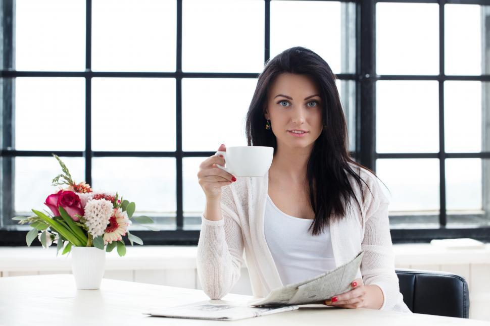Download Free Stock Photo of Woman with a cup of coffee and morning newspaper