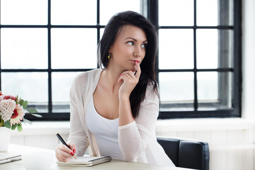 Download Free Stock Photo of Young woman at a desk, thinking