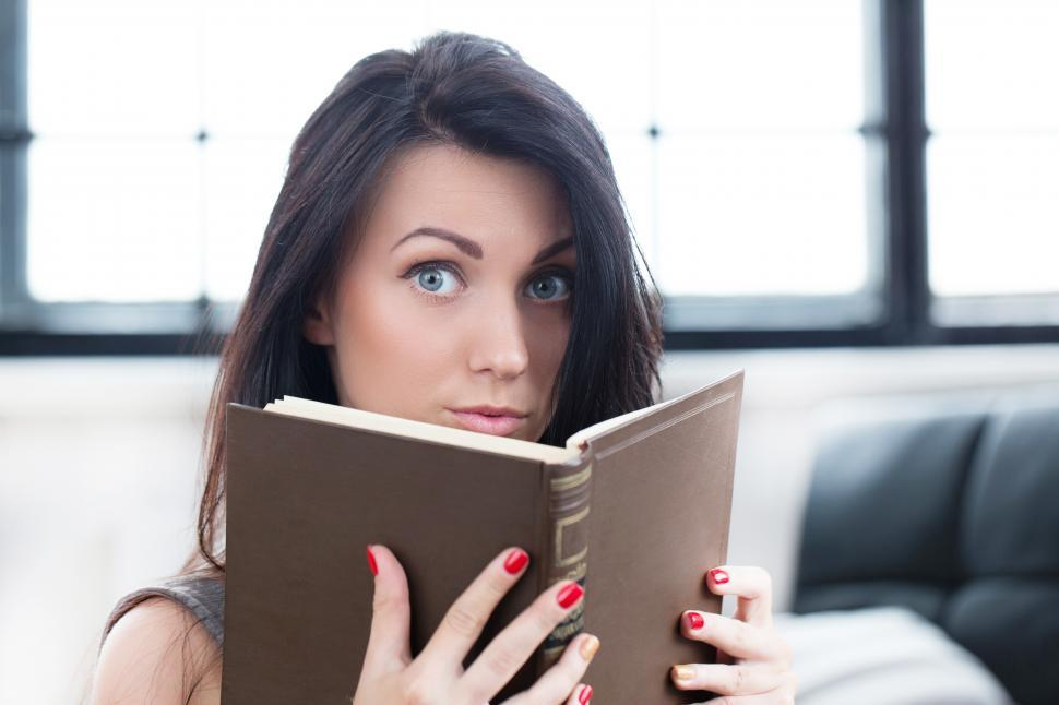 Download Free Stock Photo of Young woman reading, looking over at the camera