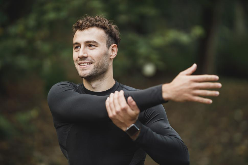 Download Free Stock Photo of Male athletic runner doing warm up exercise