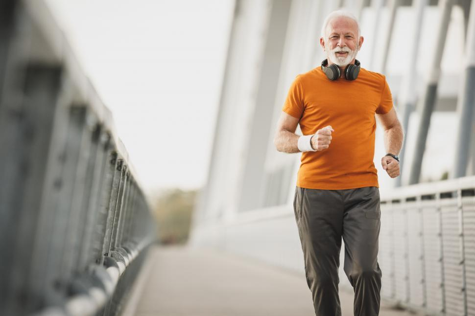 Download Free Stock Photo of Elderly man with headphones on his neck running along the bridge