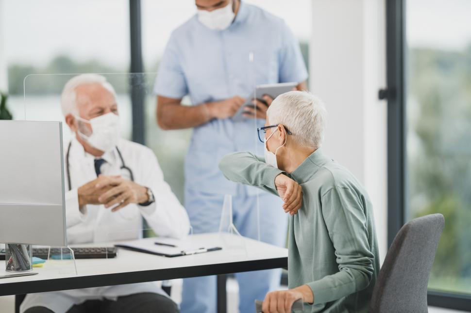 Download Free Stock Photo of Doctor and patient in clinic wearing masks - Covid-19