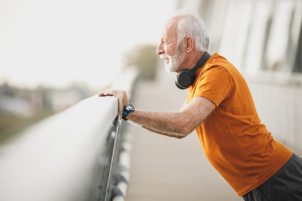 Download Free Stock Photo of Elderly man with headphones on his neck doing morning workout on