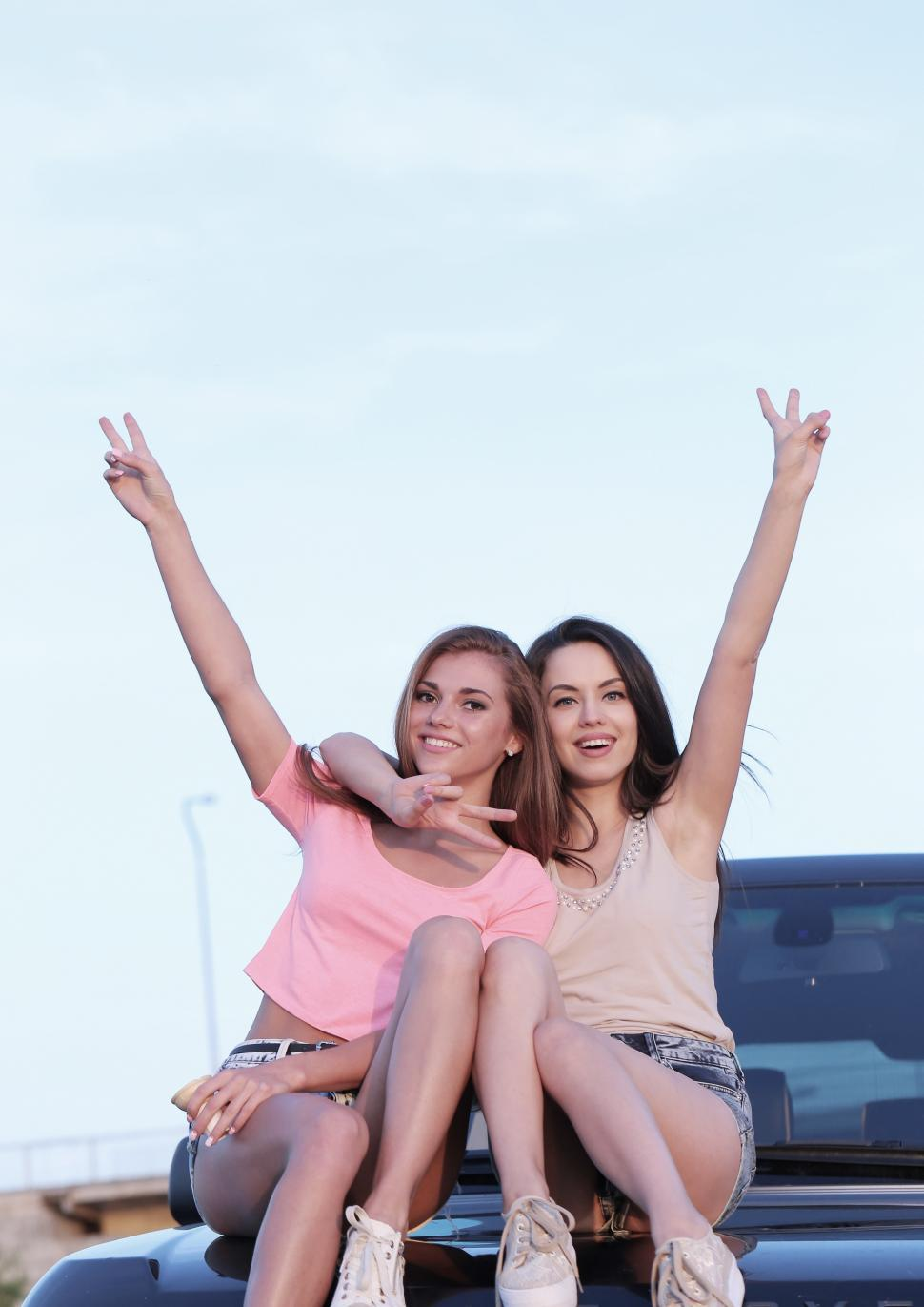 Download Free Stock Photo of Two Young Women Sitting on a Truck