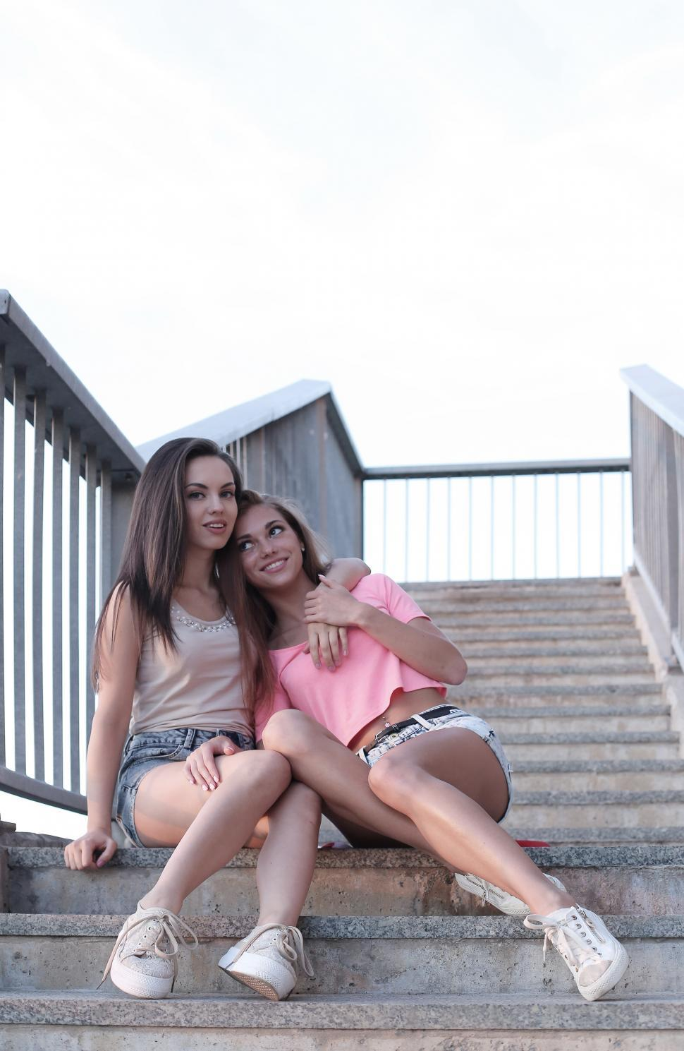 Download Free Stock Photo of Two Girls Sitting on Steps, Embracing