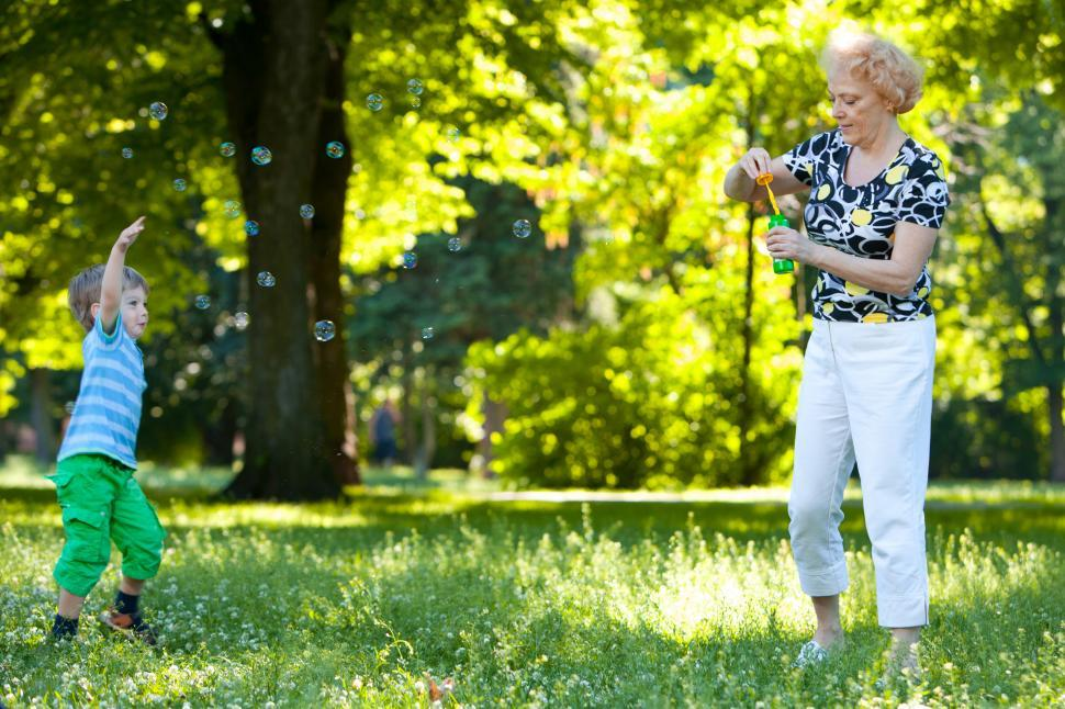 Download Free Stock Photo of Grandmother and her grandson blowing soap bubbles