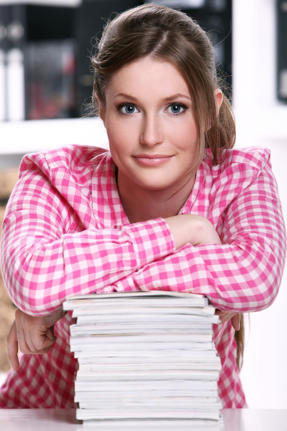 Download Free Stock Photo of Cute student girl at the desk leaning on pile of books