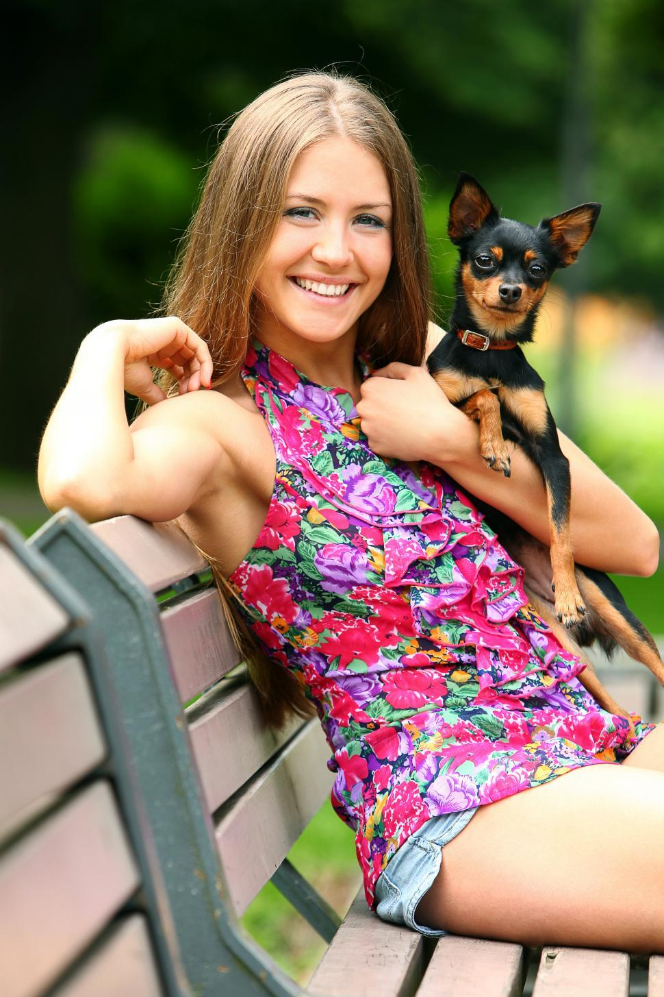 Download Free Stock Photo of Young happy girl with her cute dog on a park bench outdoors