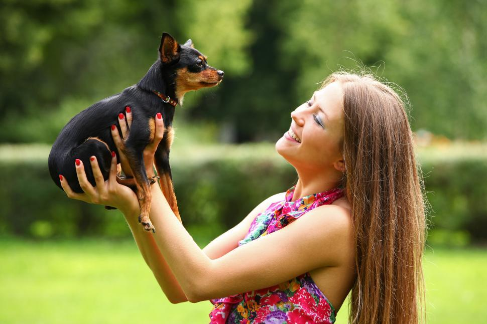 Download Free Stock Photo of Happy young woman holding up her small dog