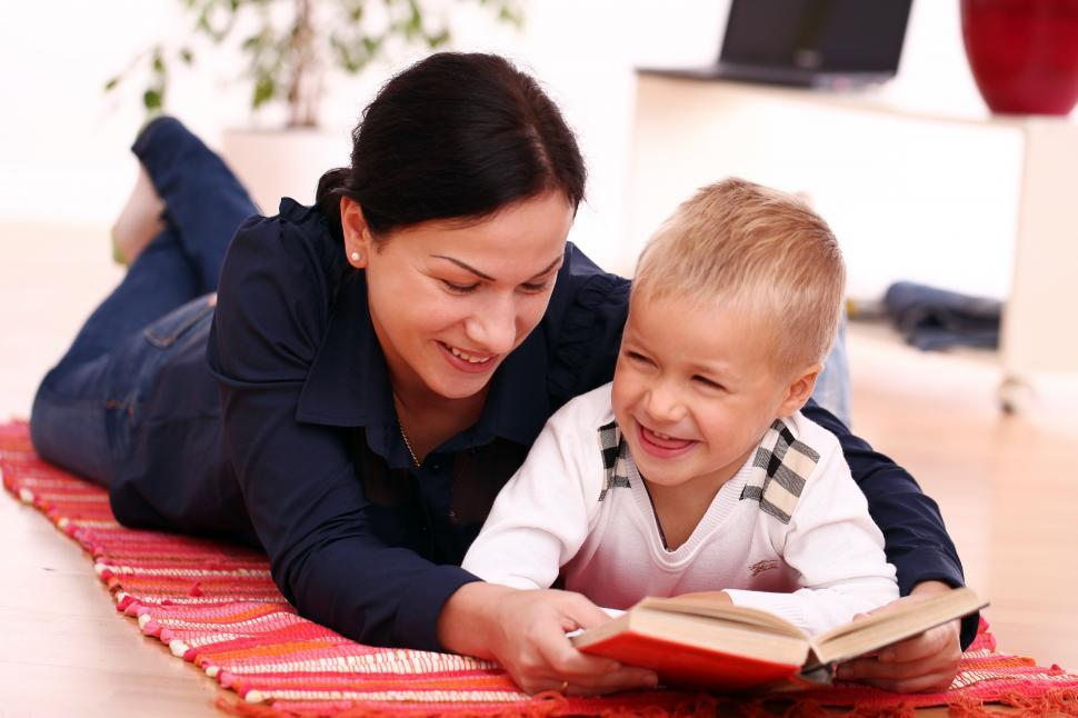 Download Free Stock Photo of Mother on the floor reading book with her child