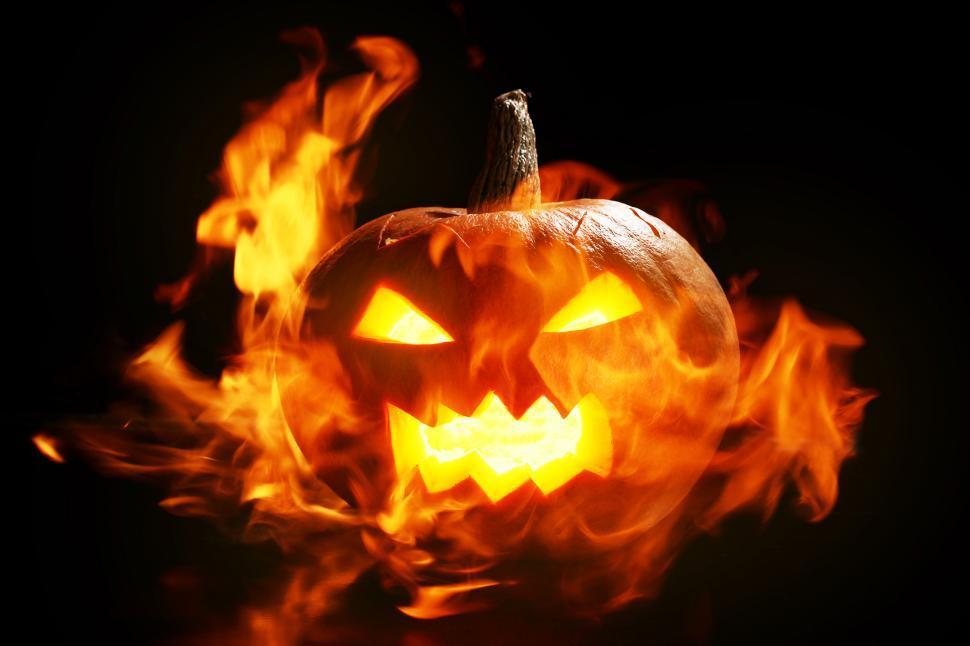 Download Free Stock Photo of Flaming jack o lantern glows in a dark scene
