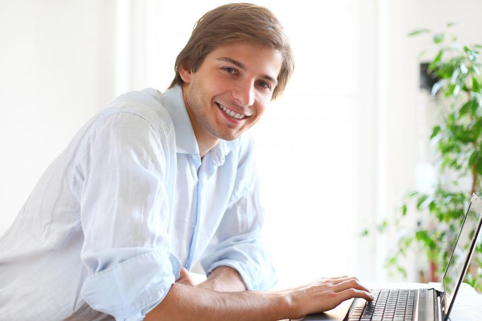 Download Free Stock Photo of Cheerful looking man at a laptop, looking at the camera