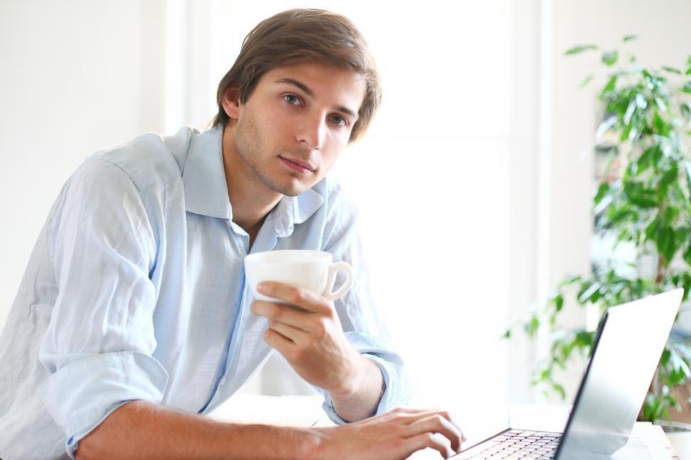 Download Free Stock Photo of Man holds a cup of coffee and looks contemplative