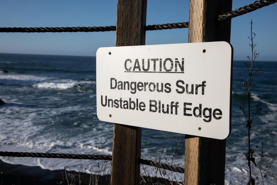 Download Free Stock Photo of Sign warns of Dangerous Surf and Unstable Bluff Edge