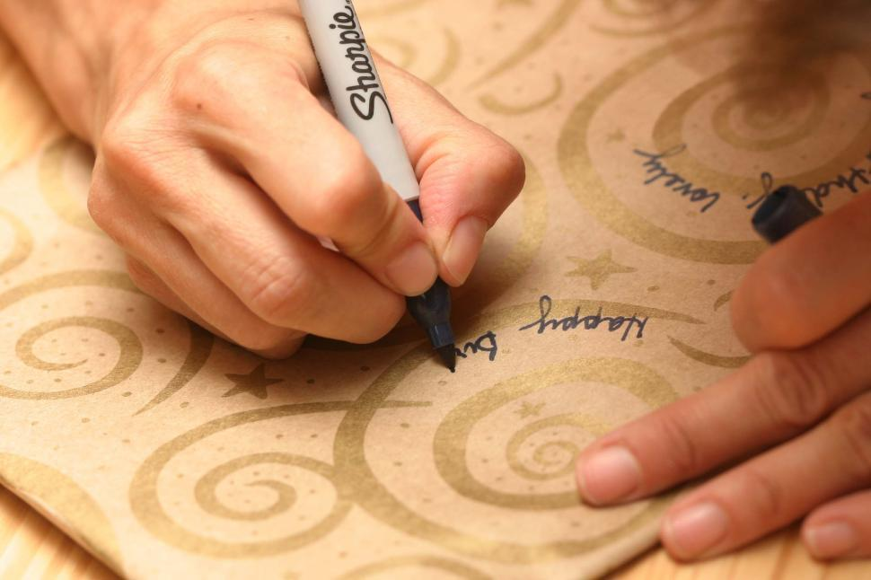 Download Free Stock Photo of hands writing sharpie marker wrapping paper ink spirals crafts happy birthday celebration presents gifts fingers pens