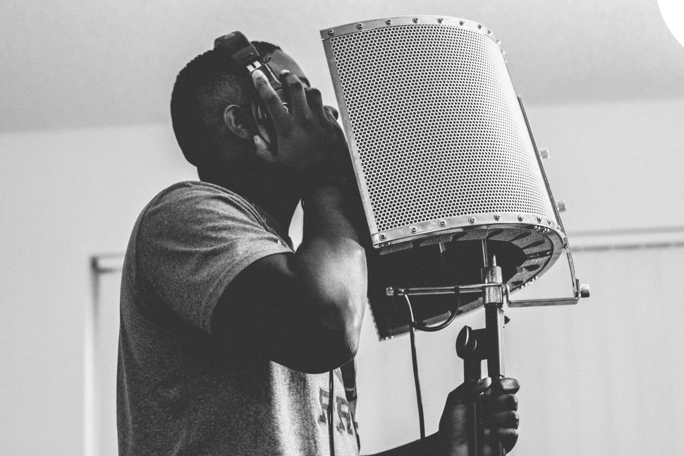 Download Free Stock Photo of Young man with microphone in music studio - b&w