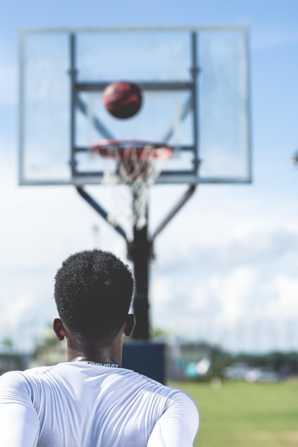 Download Free Stock Photo of Back side view of young man shooting a basketball toward a hoop