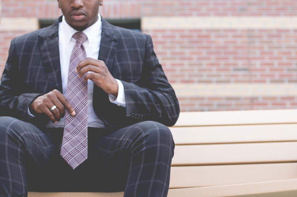 Download Free Stock Photo of Young man in blue chequered suit, sitting outside a building