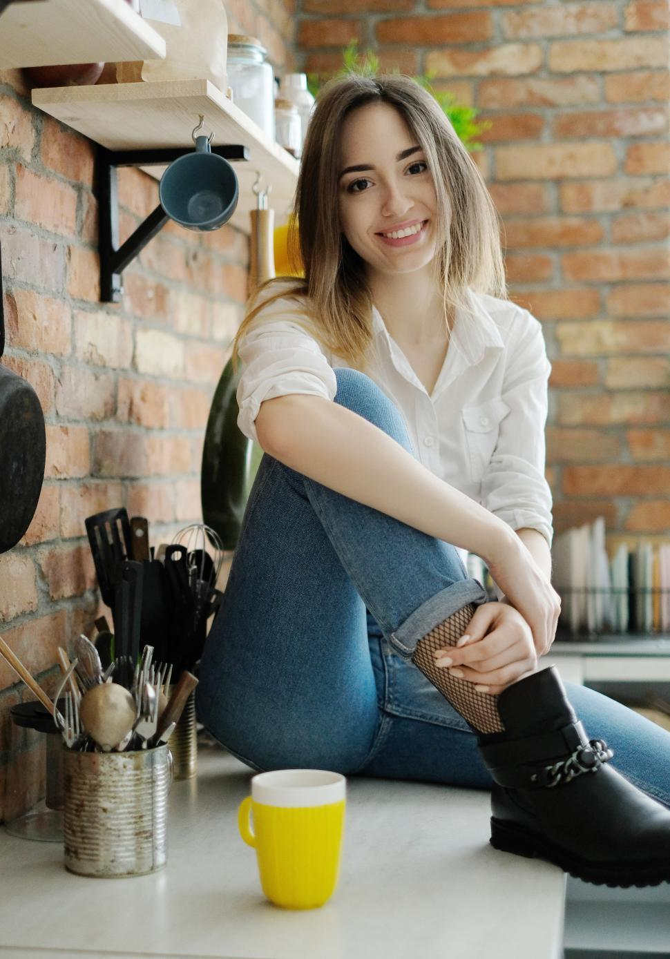 Download Free Stock Photo of Woman sitting on her kitchen counter