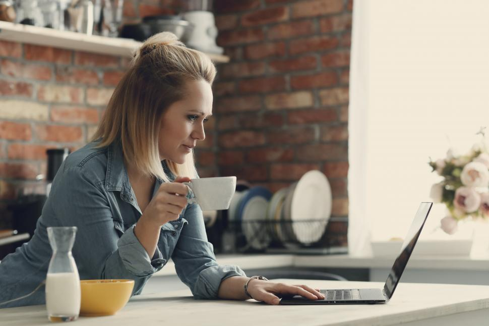 Download Free Stock Photo of Woman drinking coffee and browsing the internet