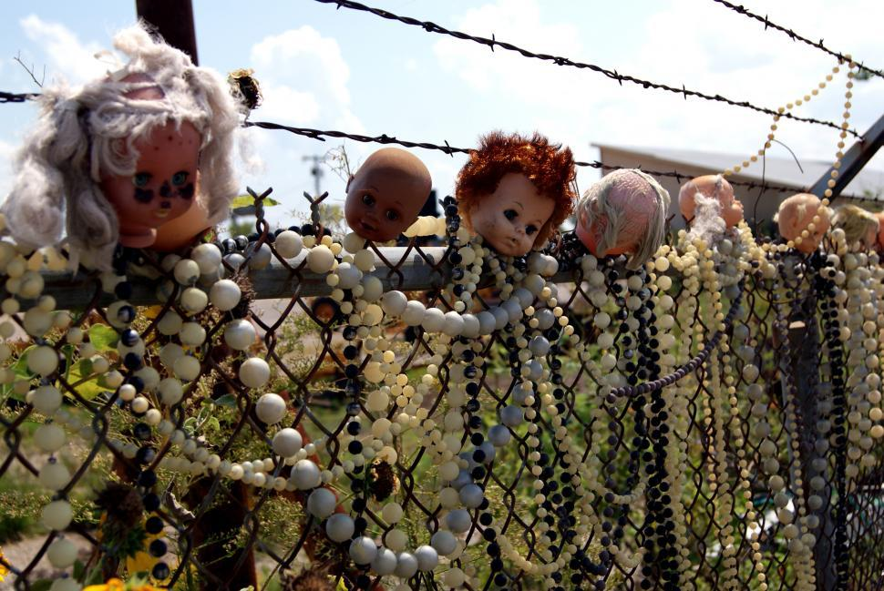 Download Free Stock Photo of Baby Doll Heads stuck on a fence
