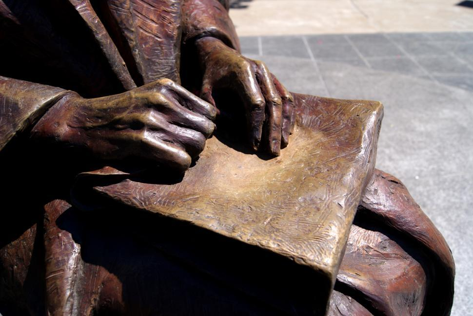 Download Free Stock Photo of Bronze statue of a women sitting with a book