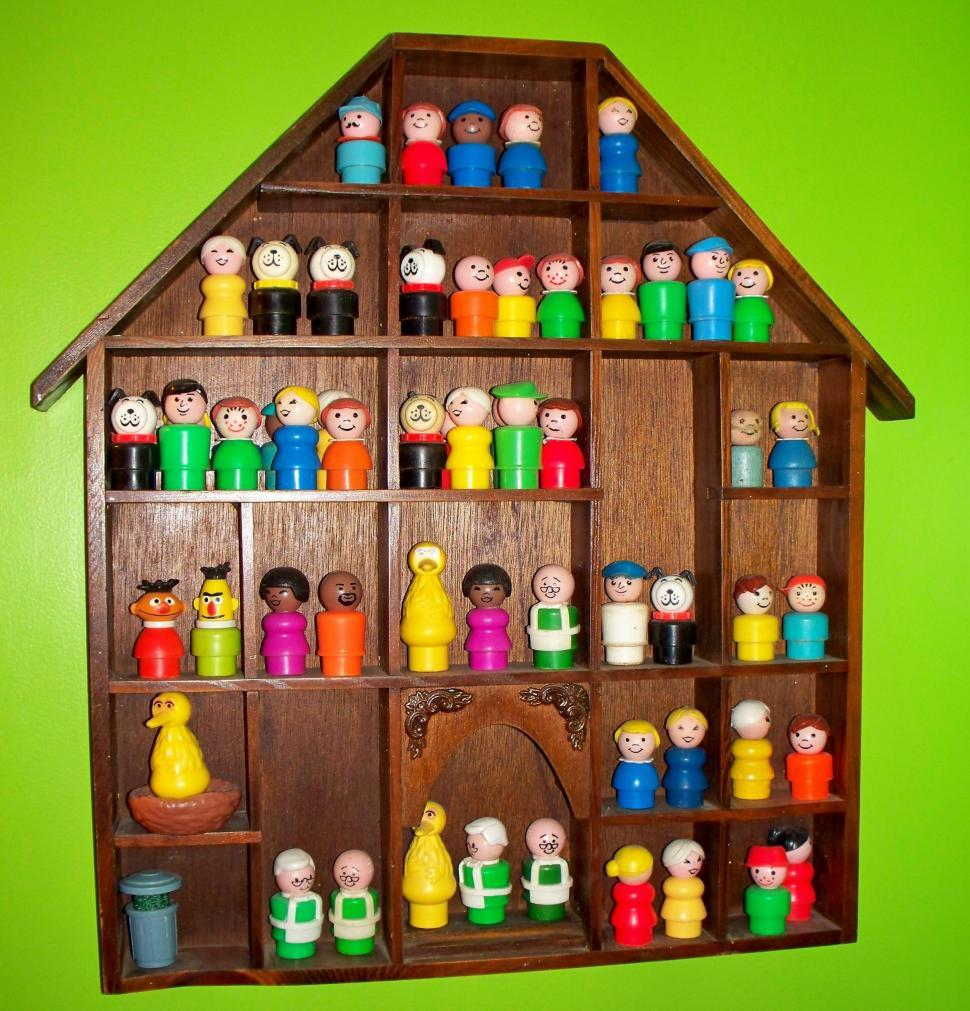 Download Free Stock HD Photo of Little plastic people toys on a shelf Online