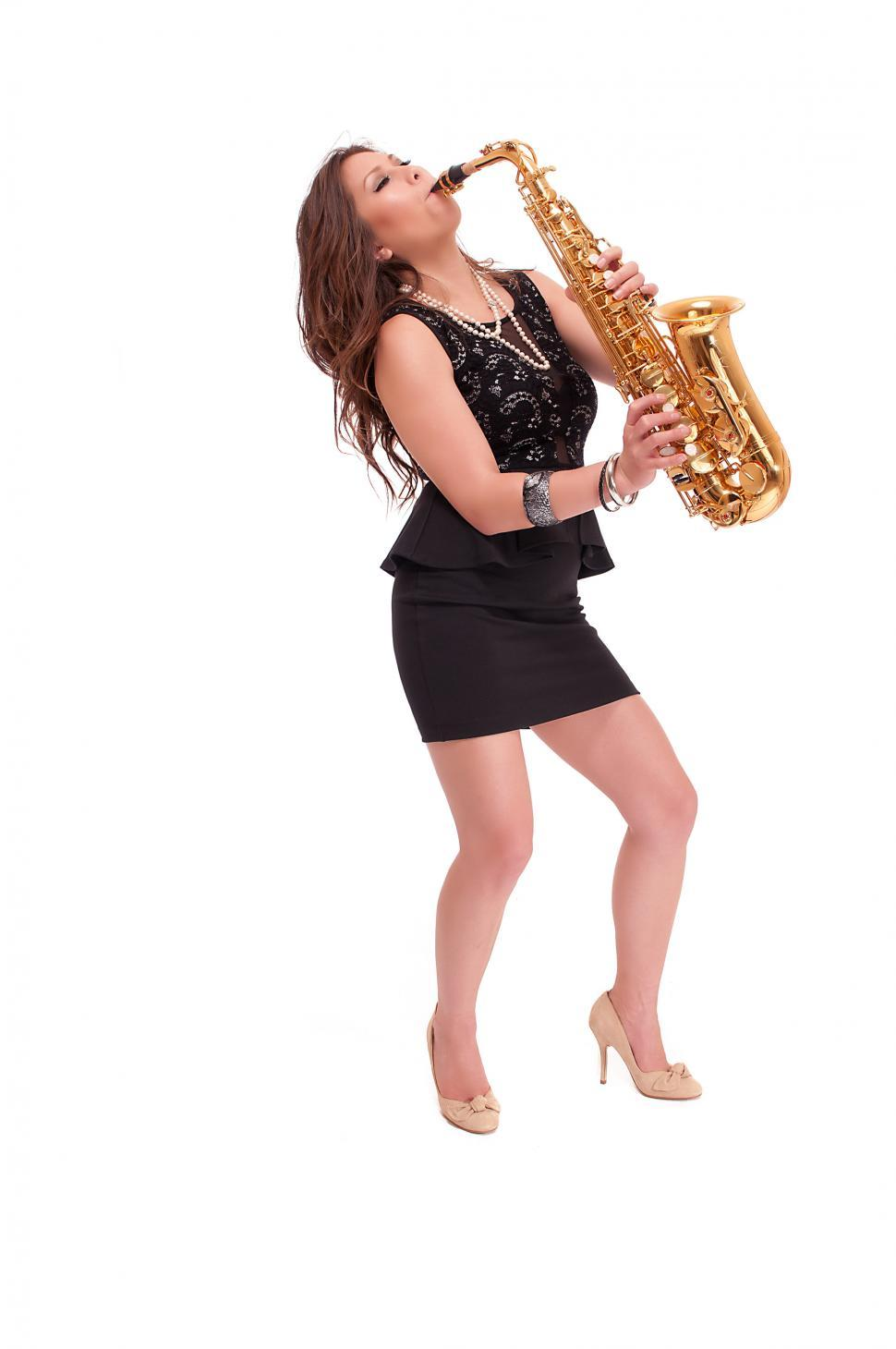 Download Free Stock HD Photo of Young woman in heels playing the saxophone Online