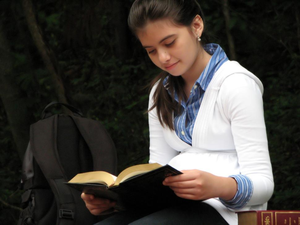 Download Free Stock Photo of A young schoolgirl reading a book outside