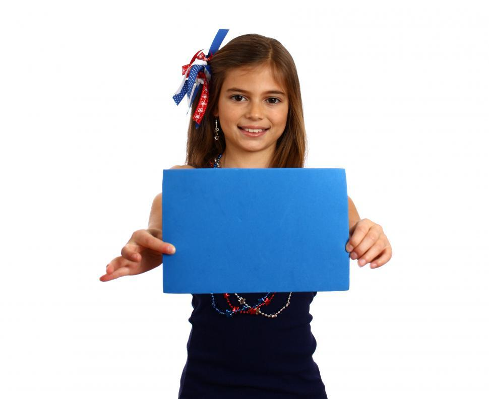 Download Free Stock Photo of A pretty young girl dressed for the 4th of July holding a blank blue sign