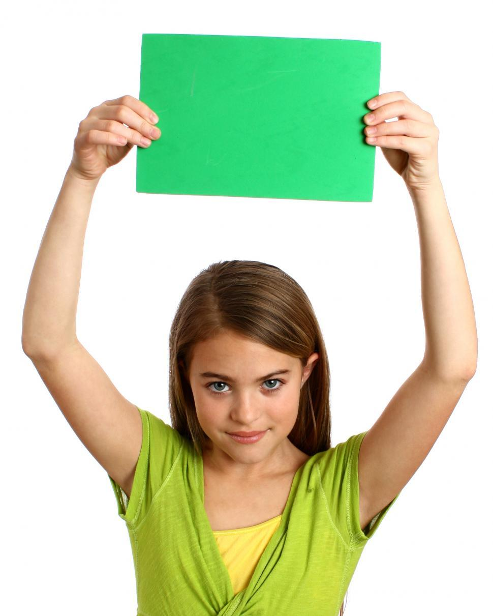 Download Free Stock HD Photo of A beautiful young girl holding a blank green sign Online