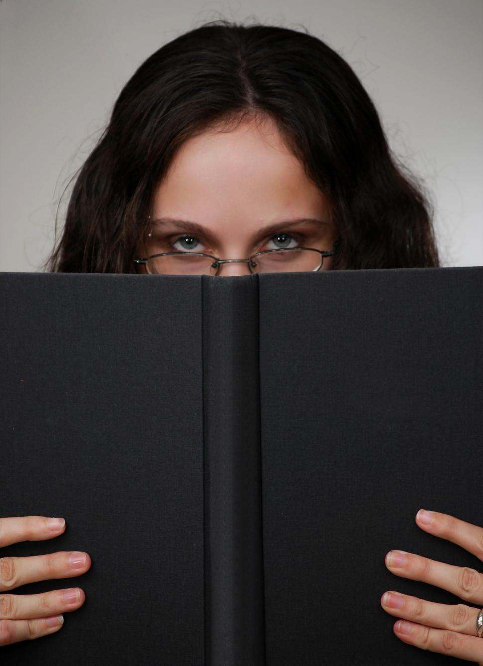 Download Free Stock Photo of A beautiful business woman looking over a book