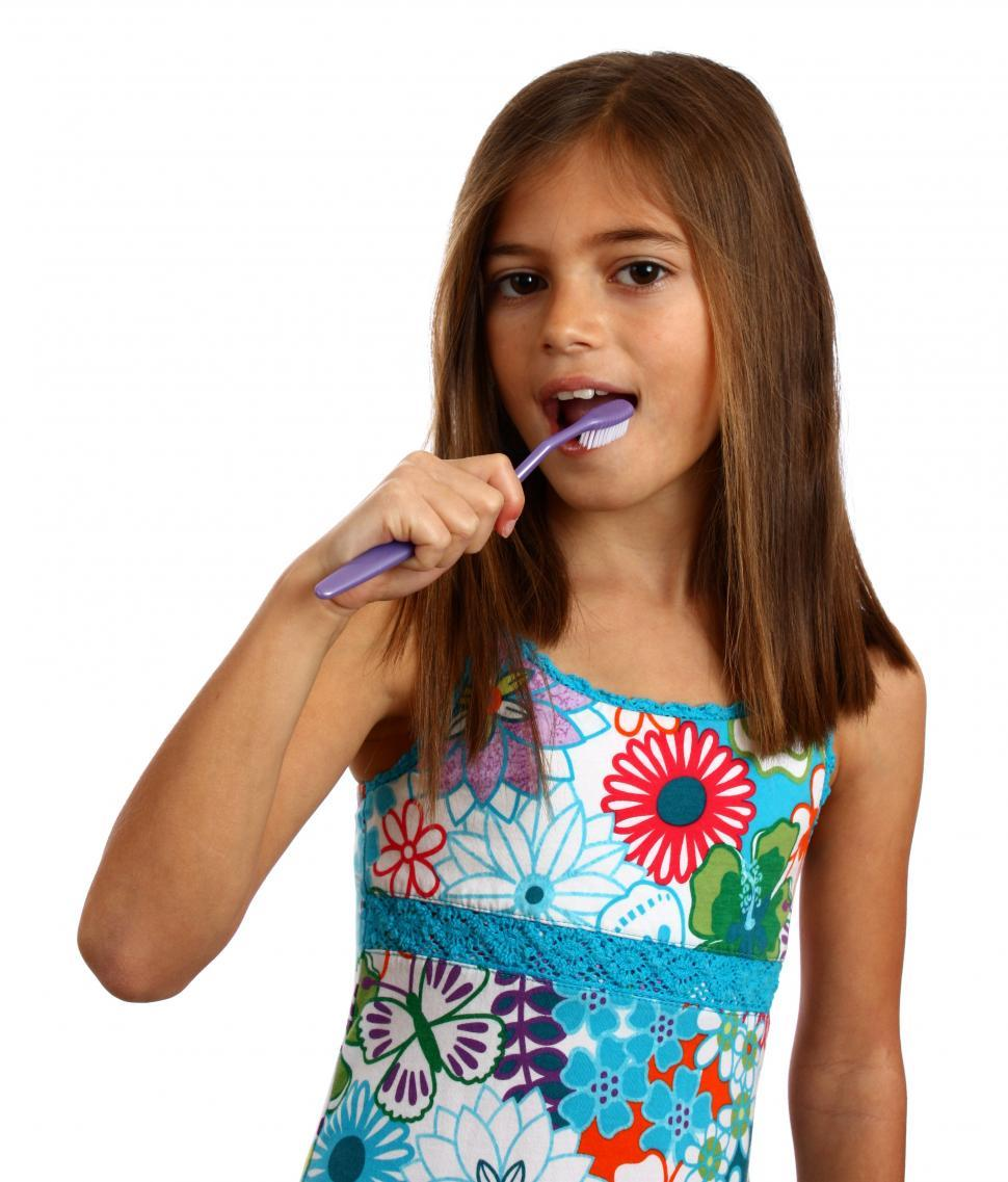 Download Free Stock Photo of A pretty young girl brushing her teeth
