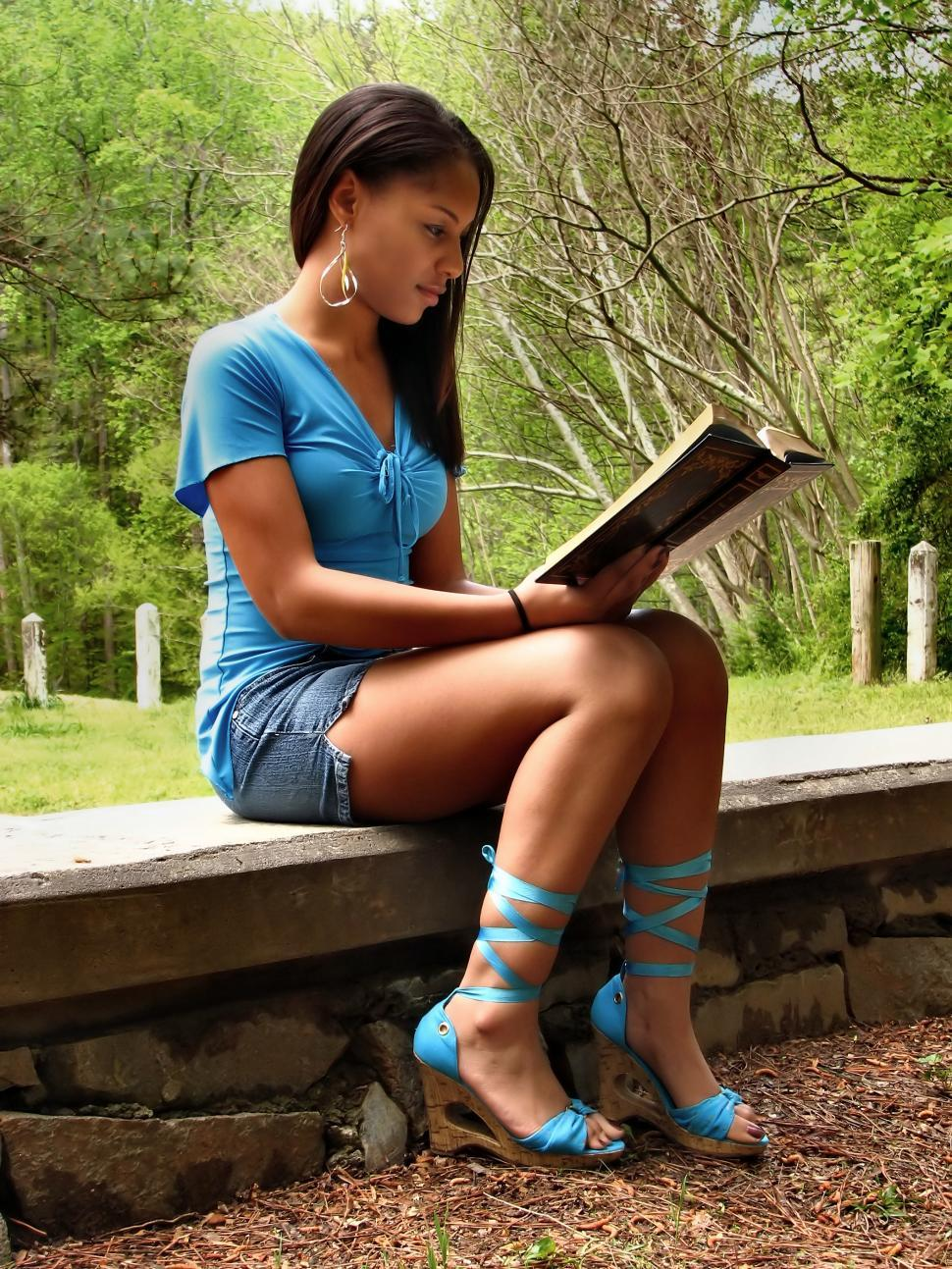 Download Free Stock Photo of A beautiful African American teen girl reading a book on a stone wall outside